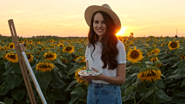 SLOW MOTION Young painter smiling at camera in the middle of sunflower field