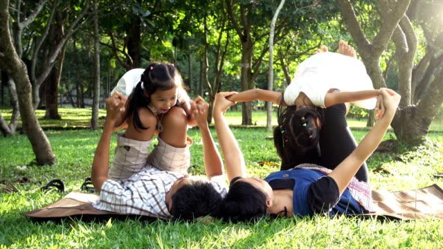 Joven padre con adorable niño niña jugando en el jardín con amor. Concepto del amor familiar en día libre o vacaciones - vídeo