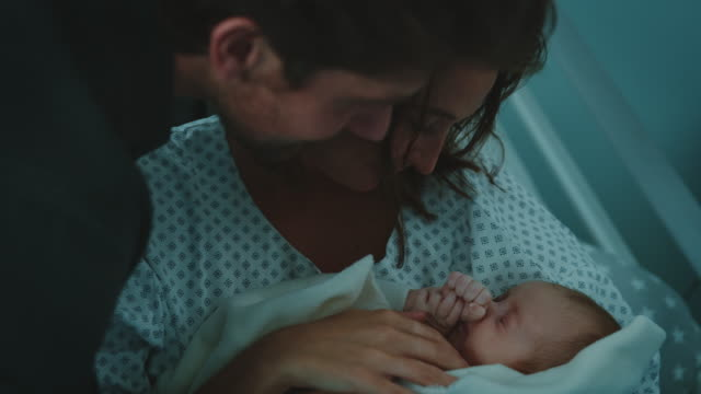 Young parents admiring newborn baby in hospital Handheld shot of nurse giving infant to parents in hospital ward. Smiling mother and father are admiring newborn. They are bonding with baby. love emotion stock videos & royalty-free footage