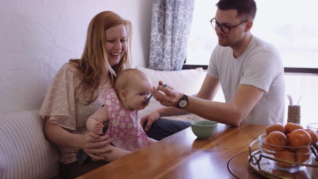 Jóvenes padres alimentando a su hija - vídeo