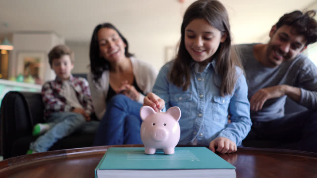 young parents teaching their kids to save money in a piggy bank on foreground all smiling - risparmi video stock e b–roll