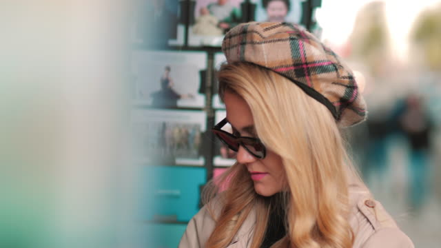 vidéos et rushes de un jeune parisien choisit une carte postale dans un magasin de rue. la fille attirante dans le béret et les lunettes de soleil achète une carte pour la mémoire du voyage - carte postale