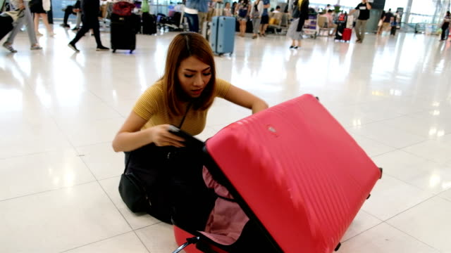 A young Passenger woman remove laptop from full of suitcase at check-in counter in airport terminal Worst Holiday Concept. Worst Holiday Concept stuffed stock videos & royalty-free footage