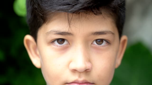 young people and emotions, portrait of serious kid looking at camera - guardare fisso video stock e b–roll