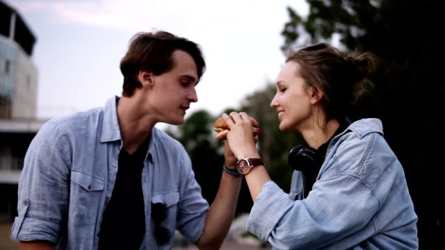 young people are biting a big burger together. sharing a food. evening dusk in the park. couple, dating, spending time together - cheeseburger filmów i materiałów b-roll