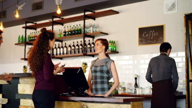 gençlerin güzel yerel kafede kahve gitmek satın almadan ve samimi işçiler müşteriler tebrik halbuki smartphone ile ödeme ve içki satan. - sipariş vermek stok videoları ve detay görüntü çekimi