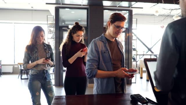 vidéos et rushes de jeunes gens sont debout en ligne achat café à emporter et paiement par téléphone mobile dans le café le matin. entreprise avec succès et le concept de banque moderne. - faire la queue