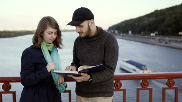 Young people at the bridge discuss the book video