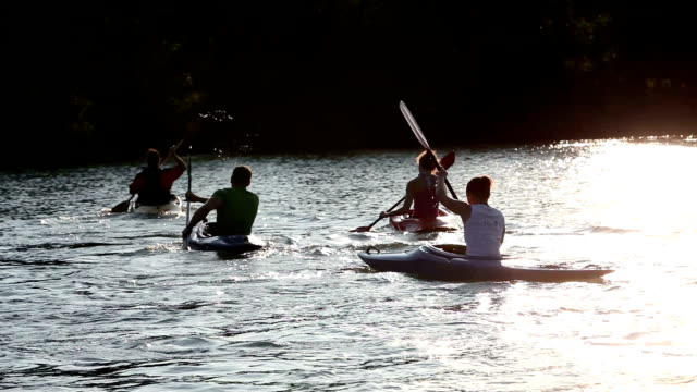 HD CRANE: Young people canoeing in the lake at sunset video