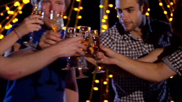 Young people clanging glasses at night party video