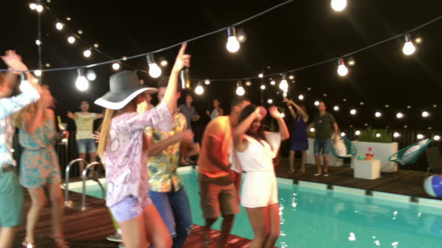 Young people dancing at a party by the pool at night Smartphone video of young people dancing by the pool at night and having a great time at the party. Shot in Slovenia. pool party stock videos & royalty-free footage
