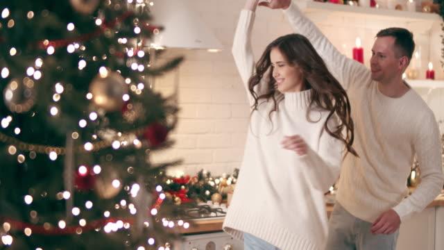 年輕人在聖誕樹旁跳舞。他們歡快地慶祝耶誕節。 - 聖誕節 個影片檔及 b 捲影像