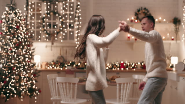 young people dancing next to the christmas tree. they cheerfully and joyfully celebrate christmas. - treedeo christmas stock videos & royalty-free footage