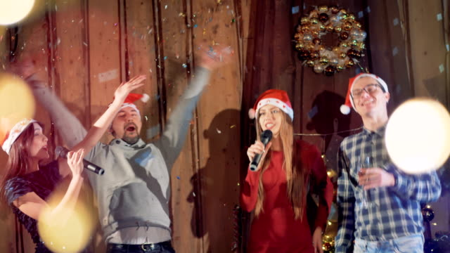 Young people dancing singing at New Year party wearing christmas hats. Slow motion. 4K. video