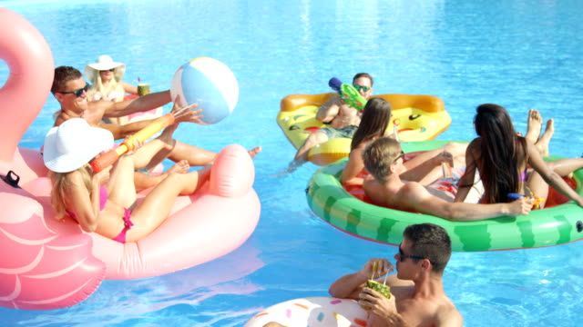 SLOW MOTION: Young people drink cocktails and have water gun fight on fun floats SLOW MOTION CLOSE UP: Playful smiling friends enjoying hot summertime on colorful floaties at pool party. Cheerful young people having fun on inflatable pizza, flamingo, watermelon and doughnut floats pool party stock videos & royalty-free footage