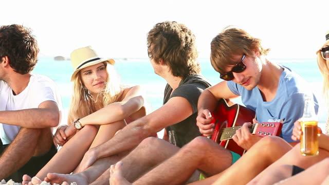 Giovani che godono di una festa in spiaggia - video