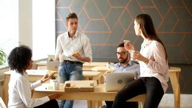 vídeos de stock, filmes e b-roll de jovens desfrutando de comer pizza juntos, almoçando no escritório - almoço