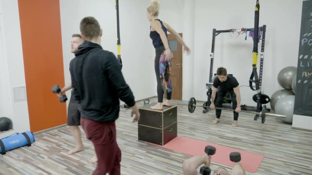 Young people exercising to lose weight at the gym while the trainer watches and corrects their work out posture video