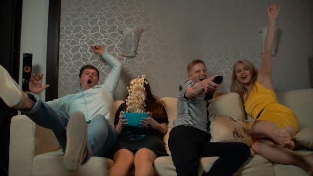 stockvideo's en b-roll-footage met jonge mensen vallen op bank om tv te kijken met pop corn - popcorn
