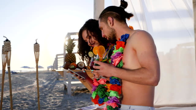 young people from Hawaii lei on neck hold in hands android, girl sitting with guy on beach and holding in hands cell phone video