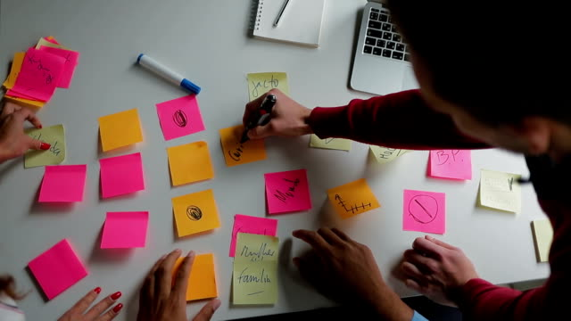 Young people glueing sticky notes on table.