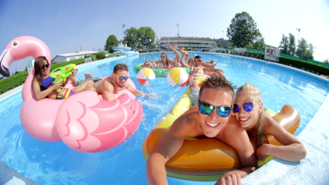 SLOW MOTION SELFIE Young people have watergun fight on fun floats at pool party SLOW MOTION SELFIE: Smiling young people enjoying on colorful floaties at pool party Happy teenagers having watergun fight splashing water on inflatable pizza, flamingo, watermelon and doughnut floats swimwear stock videos & royalty-free footage