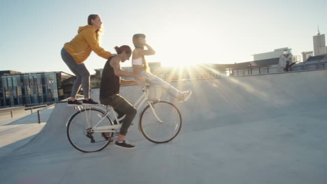 Young people having fun a ride on a cycle Man on bicycle with a female friend sitting on the handlebar and another standing in back enjoying and raising their hands. handlebar stock videos & royalty-free footage