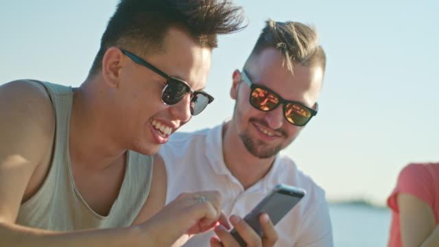 Jóvenes divirtiéndose en la playa utilizando teléfonos - vídeo