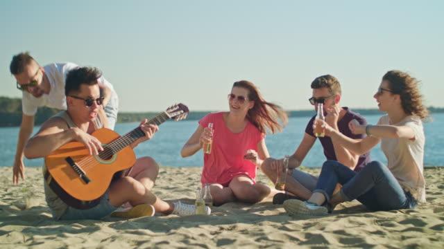 若い人々 とビーチで楽しく ビデオ