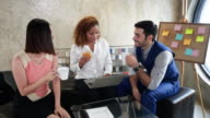 istock Young people having lunch in an office.black business woman eating hamburger and asia beauty girl drink coffee and caucasian white man holding cup of coffee with laptop notebook on table in canteen 1213108121