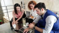 istock Young people having lunch in an office.black business woman eating hamburger and asia beauty girl drink coffee and caucasian white man holding cup of coffee with laptop notebook on table in canteen 1213110855
