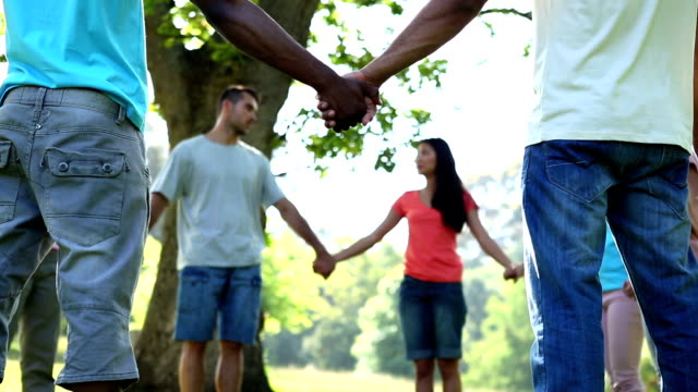 Young people holding hands in a circle video