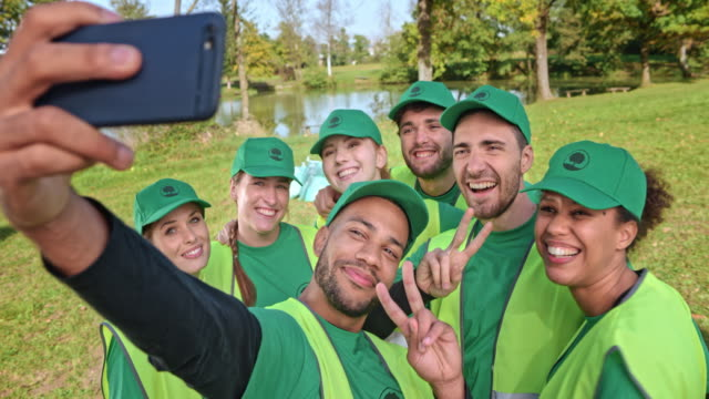 Young people in a local clean-up organization taking selfies in the meadow