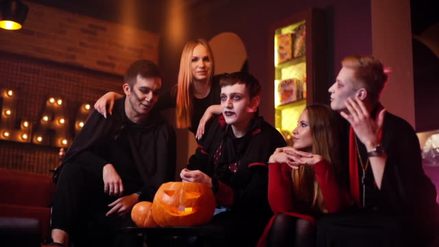 Young people in costumes are celebrating Halloween in cafe Young people are celebrating Halloween in cafe. Group of young cheerful guys and girls dressed in holiday costumes are sitting in room with red walls. Carved pumpkin on table. Shot in slow motion count dracula stock videos & royalty-free footage