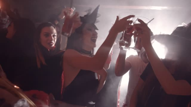 young people in halloween costumes toasting with drinks at bar - halloween video stock e b–roll