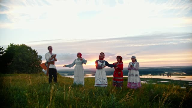 young people in russian traditional clothes having fun on the field - singing, dancing - славянская культура стоковые видео и кадры b-roll