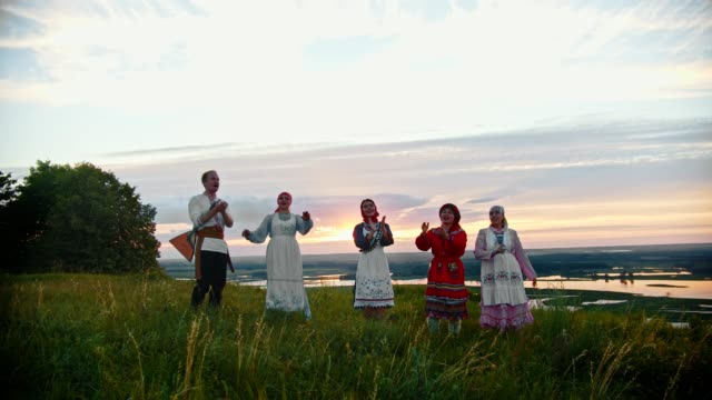 young people in russian traditional clothes having fun on the field - dancing and clapping their hands. - славянская культура стоковые видео и кадры b-roll