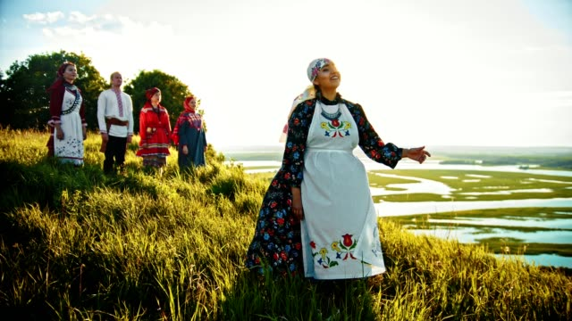 young people in russian traditional clothes standing on the field and enjoying the view on sunset - славянская культура стоковые видео и кадры b-roll