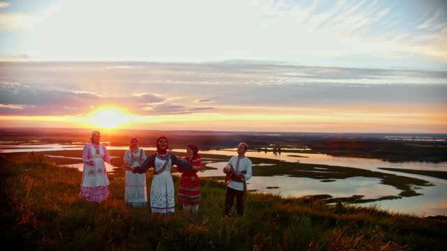 young people in russian traditional clothes standing on the field on a background of beautiful sunset and singing. - славянская культура стоковые видео и кадры b-roll