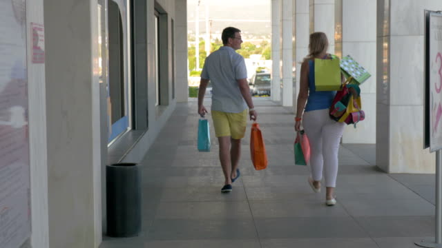 Young people leaving trade centre being happy with shopping Young couple walking out shopping centre with many colorful bags. Satisfied with purchases they making their way along the street goodbye single word stock videos & royalty-free footage