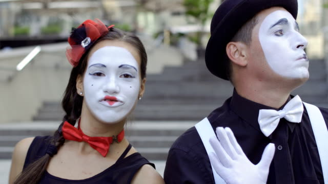 Young people mimes playing their expressions on camera Two funny mimes play a scene. Girl and guy gesticulates their facial expressions. Young amateurs earn money showing people small funny scenes at urban streets. greasepaint stock videos & royalty-free footage
