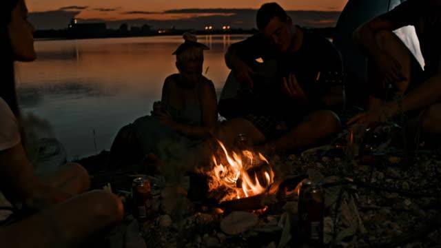 slo mo 젊은이들이 호수 에서 모닥불로 기타를 부르고 연주합니다. - 20 29세 스톡 비디오 및 b-롤 화면