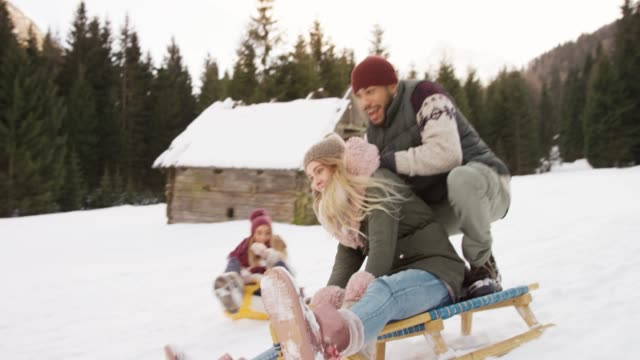 slo mo young people sliding down the hill and a couple on the snow sled falls down laughing - scivolo video stock e b–roll