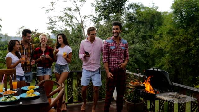 Téléphones intelligent de jeunes gens qui parlent à l'aide de cellules tandis que le Latin Man cuisson Barbecue amis groupe rassemblement sur la Communication de la terrasse d'été - Vidéo
