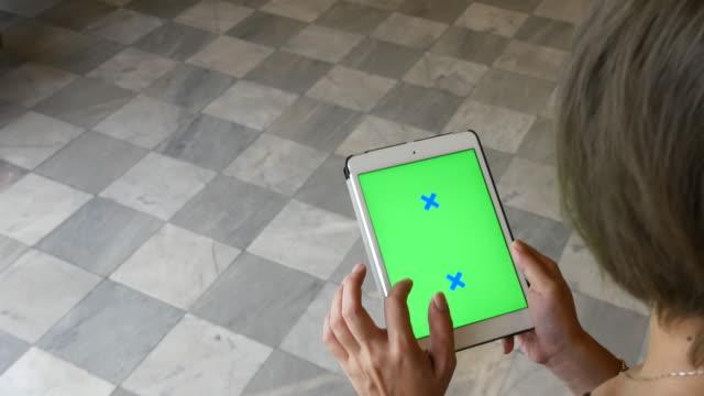 vídeos de stock e filmes b-roll de jovens a caminhar para usando tablet digital, verde ecrã - stabilized shot