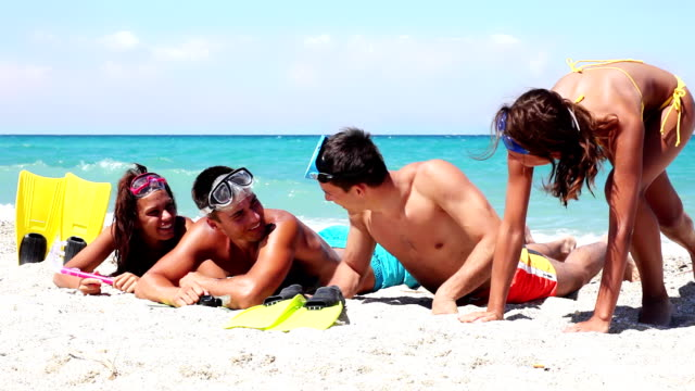 vídeos de stock, filmes e b-roll de jovens com equipamento de mergulho descansando na praia. - pessoas bonitas