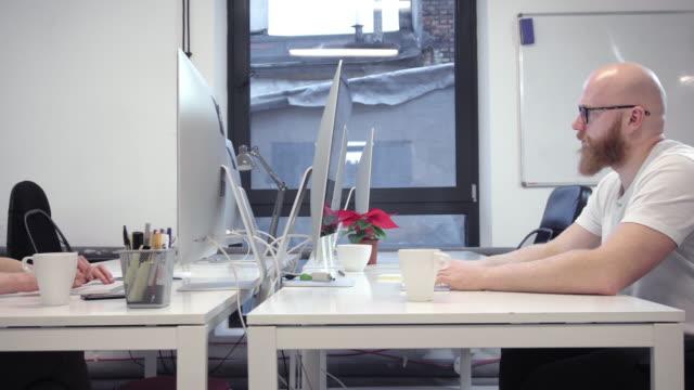 작은 사무실에서 일 하는 젊은 사람들 - 와이드 샷 스톡 비디오 및 b-롤 화면