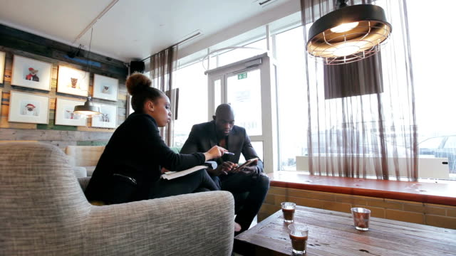 Young people working on new business strategy at cafe Two business people sitting in a cafe discussing work on digital tablet. Young people working in office cafeteria with woman explaining business strategy to male colleague. small business saturday stock videos & royalty-free footage