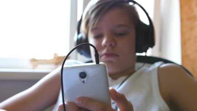 en ung person lyssnar på musik med hjälp av en hörsnäcka och telefon. killen är i rummet nära fönstret - människorygg bildbanksvideor och videomaterial från bakom kulisserna