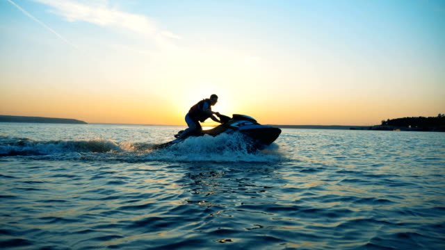 Young person riding a waverunner on a sunset background, side view.